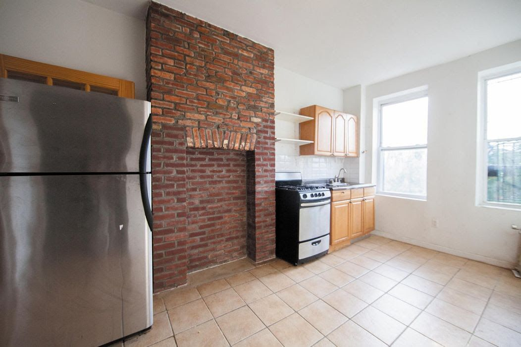 A kitchen with a fridge, exposed brick, a stove and wood cabinetry.