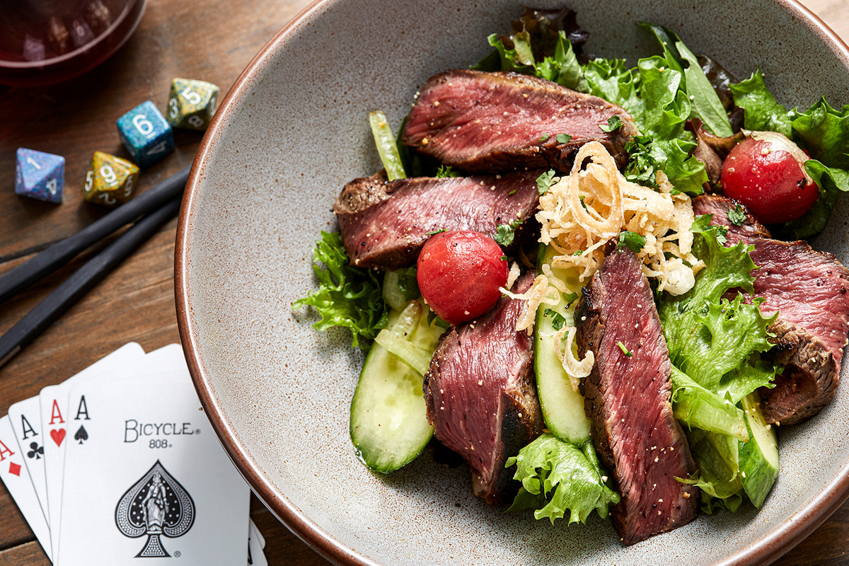 A steak salad in a bowl surrounded by cards and dice.