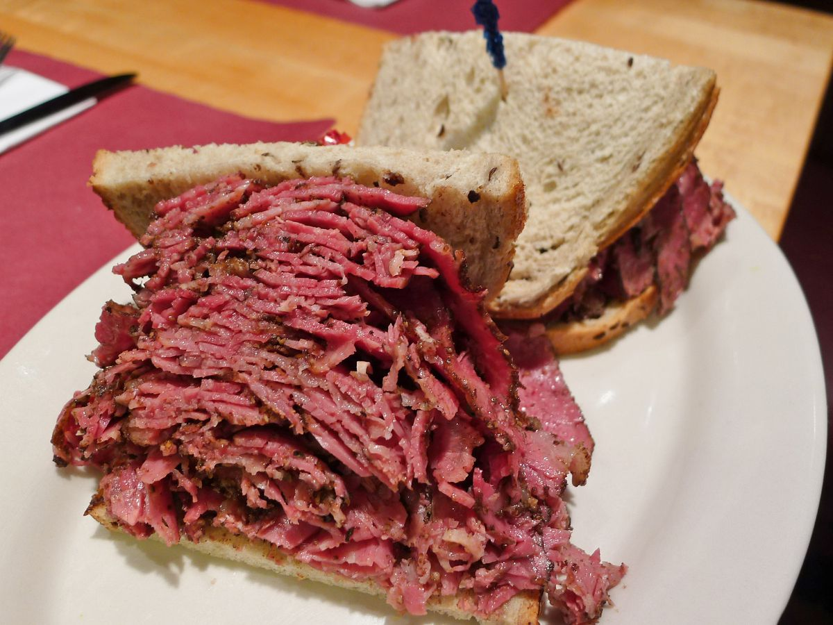 A piece of rye bread is precariously placed on top of a heap of pastrami