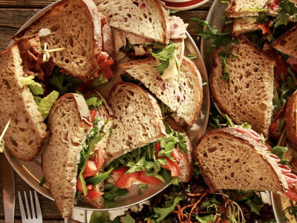 A pile of sandwiches on rye bread at Conscious Eatery in Georgetown topped with lettuce