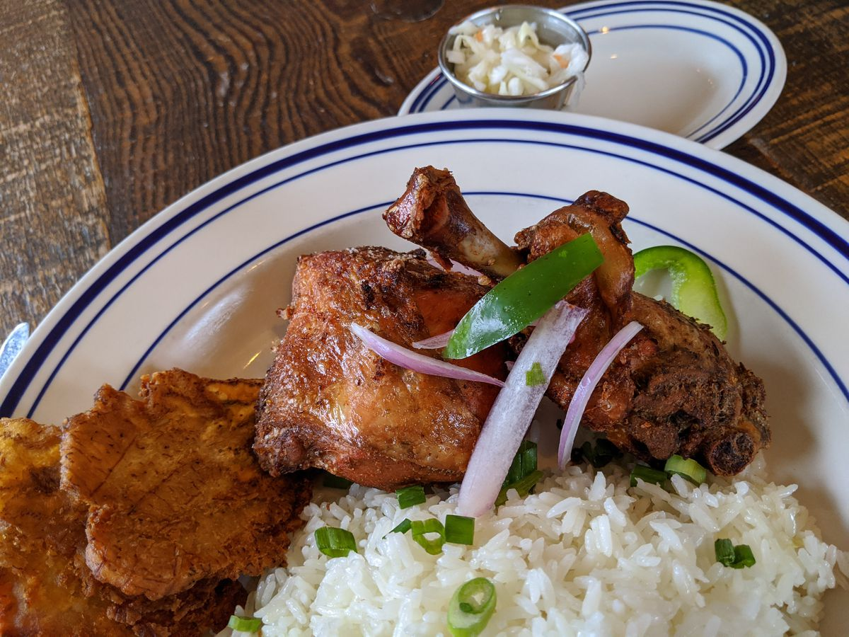 Two pieces of fried chicken with green plantains, rice, and slaw.