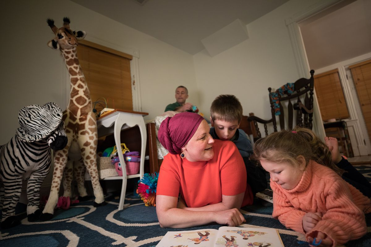 Sarah Mancoll, an advocate for including women in more clinical trials of medication, reads to her children Samuel and Maayan, ages 5 and 3, while husband Peter cares for Abraham, 1, in their Takoma Park, Md., home on Thursday, Oct. 18, 2018. Mancoll suff