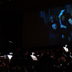 Sterling Poulson directs the Choral Arts Sosiety of Utah and the Days of '47 Orchestra while video is shown of well-known moments in the Olympic Torch's trek through Utah during the Days of '47 Pops Concert at Abravanel Hall, Monday, July 8, 2002.