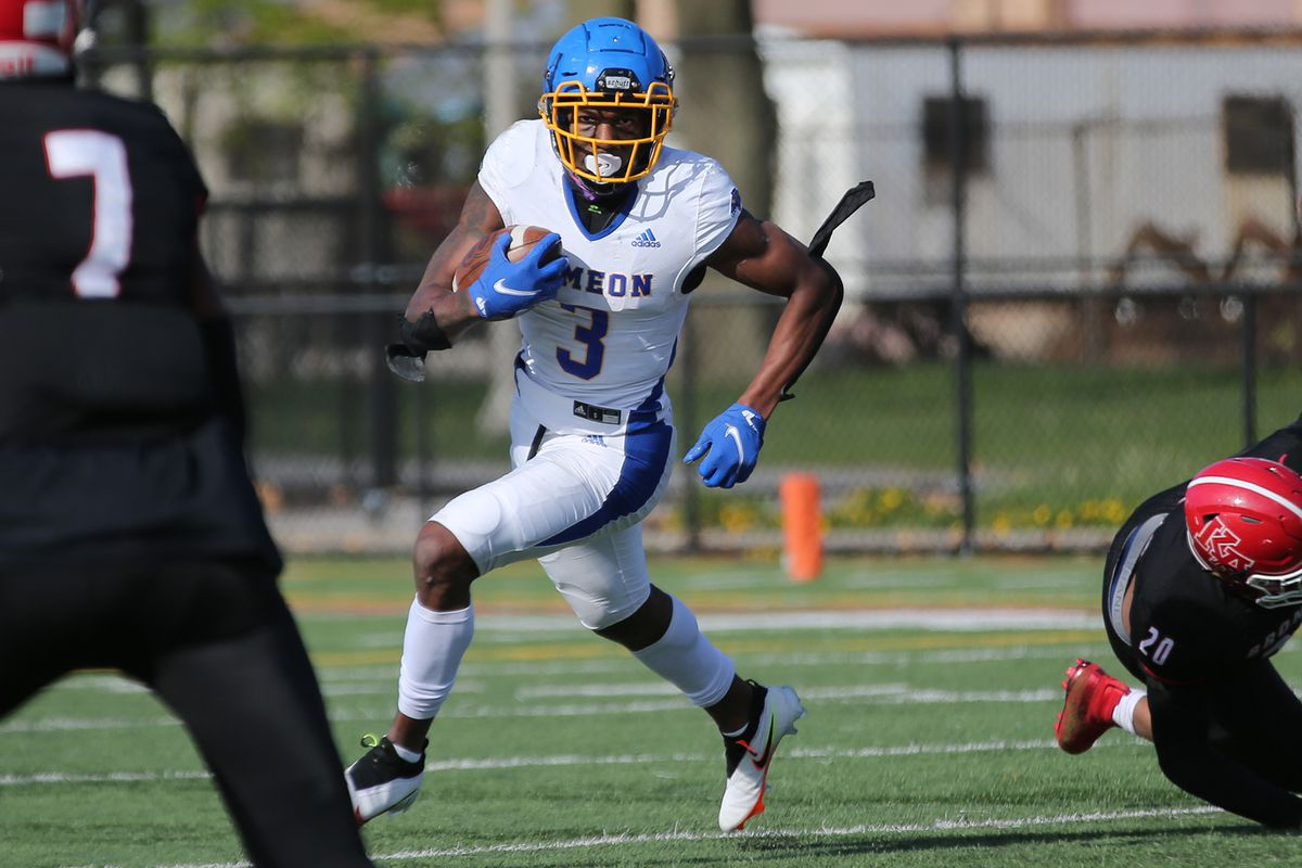 Simeon's George Gumbs (3) comes around end and cuts upfield as the Wolverines play Kenwood.