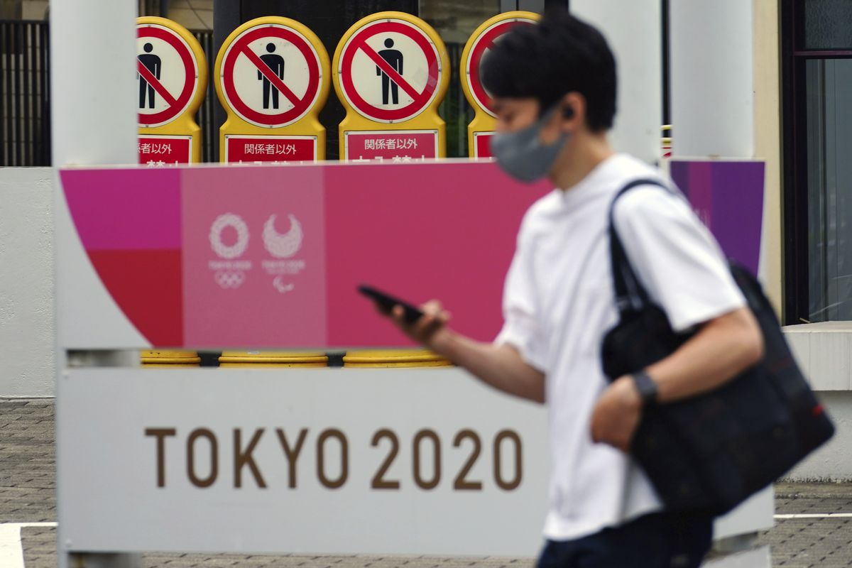 A man wearing a protective mask to help curb the spread of the coronavirus walks past a banner for the Tokyo 2020 Olympic and Paralympic Games  in Tokyo.