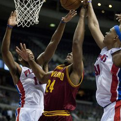 Detroit Pistons' Greg Monroe, left, and Charlie Villanueva, right, defend a shot by Cleveland Cavaliers' Samardo Samuels (24) during the first half of an NBA basketball game Tuesday, April 17, 2012, in Detroit.