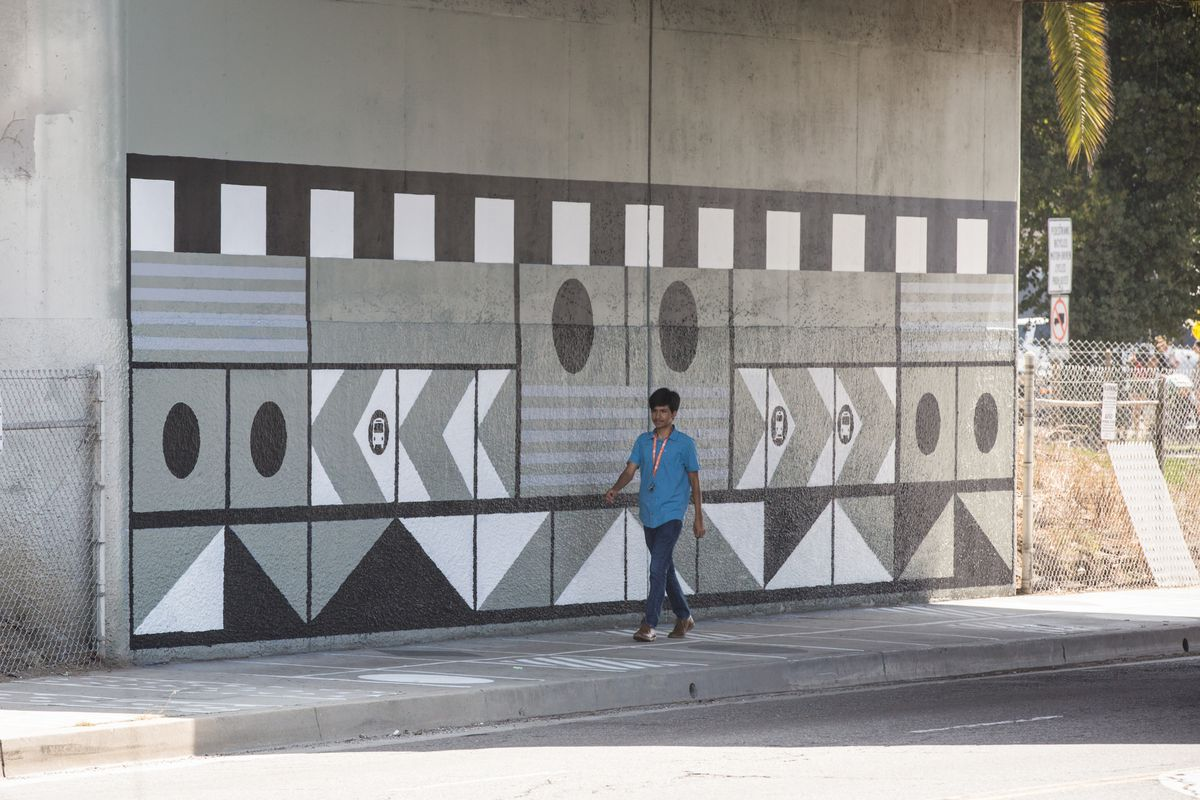 Boy walks below overpass