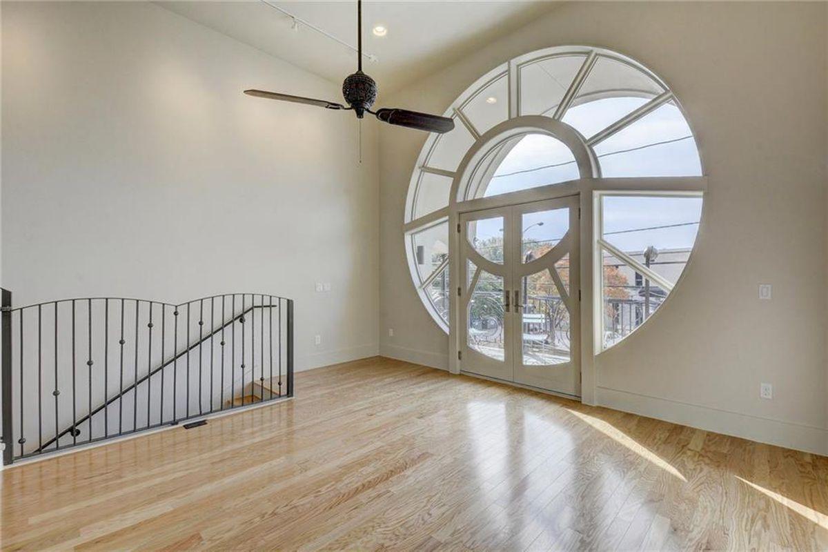 New condo living room with wood floors and huge circular window