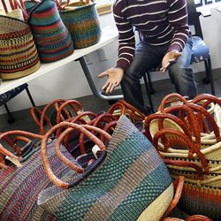Doctor Abio Ayeliya sells baskets from his home village in Ghana during a volunteer open house event at the Utah Refugee Education and Training Center in Salt Lake City, Saturday, Jan. 9, 2016. Abio Ayeliya uses the profits for a foundation in his home country.