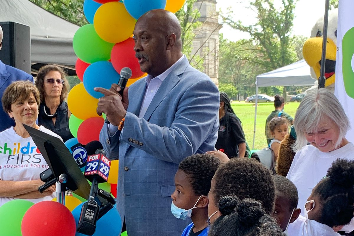 U.S. Rep. Dwight Evans speaks at Children First event Thursday. The organization's executive director, Donna Cooper, is to his left wearing the Children First T-shirt, and there are several children and a few other adults around him.