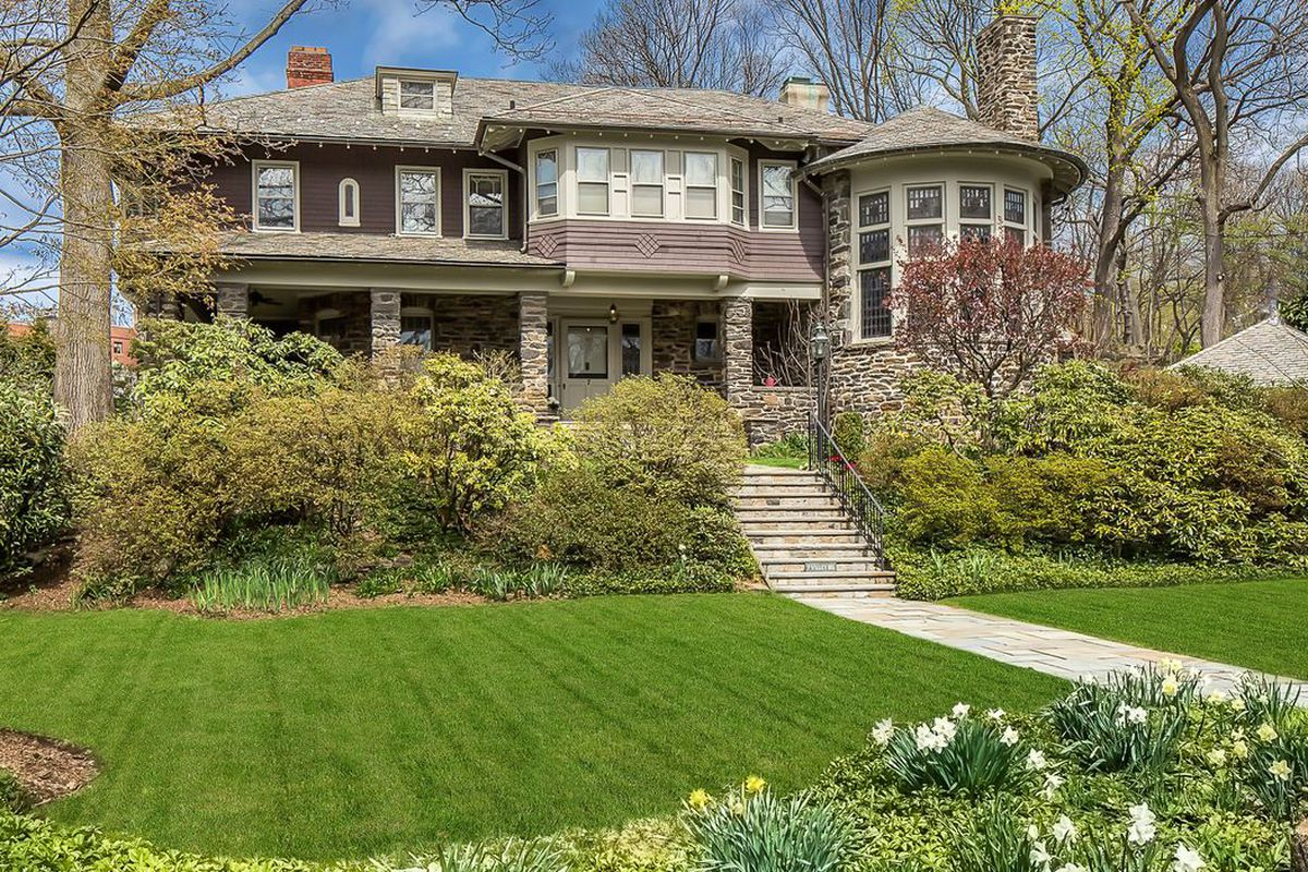 Exterior shot of Queen Anne Shingle style home with stone and shingle facade, slate roof, turret, and wraparound porch.