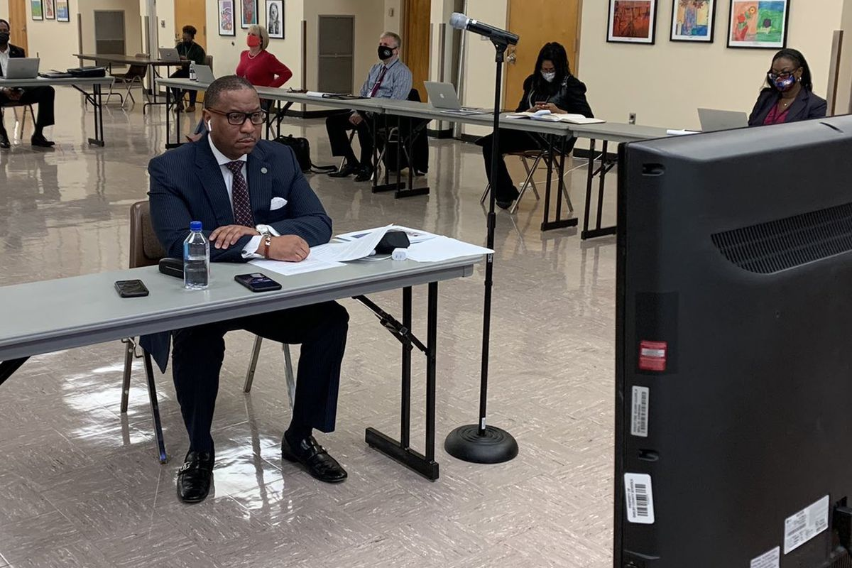 Superintendent Joris Ray sits at a table in the central office auditorium looking at a screen to join the virtual school board committee meeting.