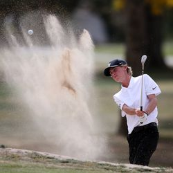 Cooper Jones of Lone Peak hits out of a sand hazard as he and other boys compete in the 6A boys state tournament at Davis Park Golf Course in Kaysville on Tuesday, Oct. 5, 2021.