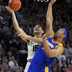 Utah State guard Abel Porter (15) shoots as San Jose State forward Ralph Agee defends during the first half of an NCAA college basketball game Tuesday, Feb. 25, 2020, in Logan, Utah.
