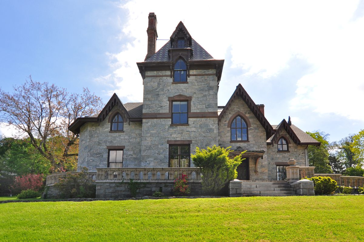 Exterior shot of stone house in Gothic Revival stile with spires and gables on a manicured lawn.