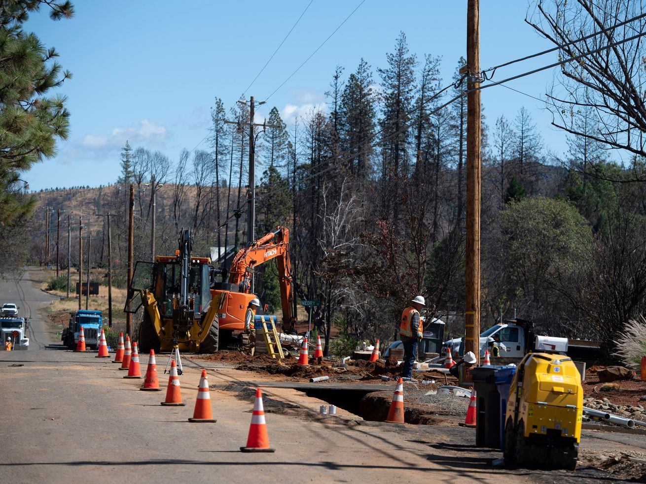 Pacific Gas & Electric workers install conduit in trenches for underground electric lines along a tree-lined road.