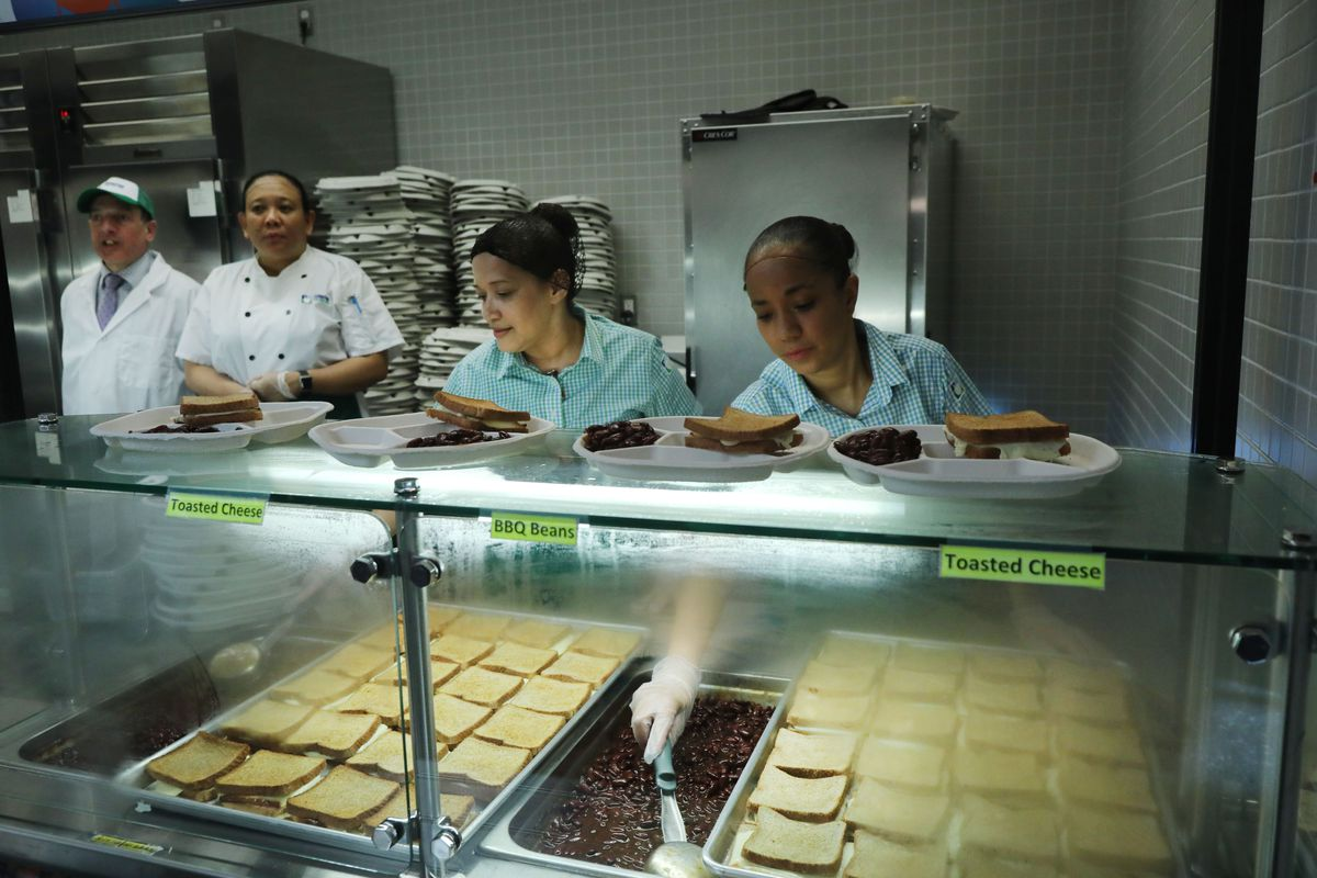 Cafeteria workers in a school stand behind their hot food serving line.