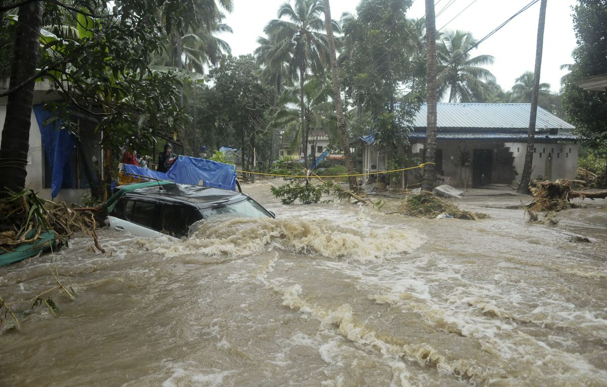 A car is submerged as roads and houses are engulfed in water following heavy rain and landslide in Kozhikode, Kerala state, India, Thursday, Aug. 9, 2018.