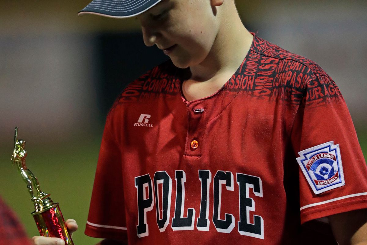 Appleton Police's Jon Nicolaison (13) checks out his second place trophy during the Major Baseball City Championship game Wednesday, June 30, 2021, at Scheels USA Youth Sports Complex in Appleton