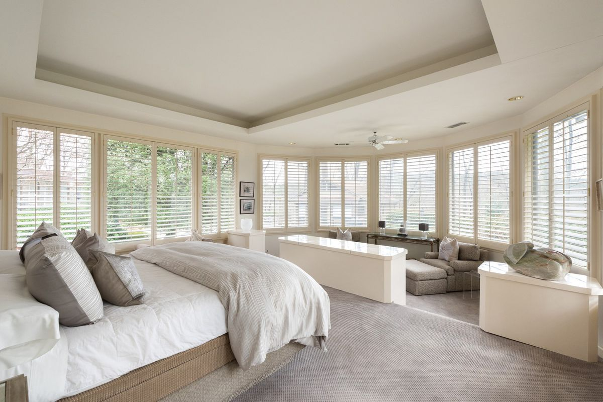 A huge white master bedroom with a white bed and gray chairs.