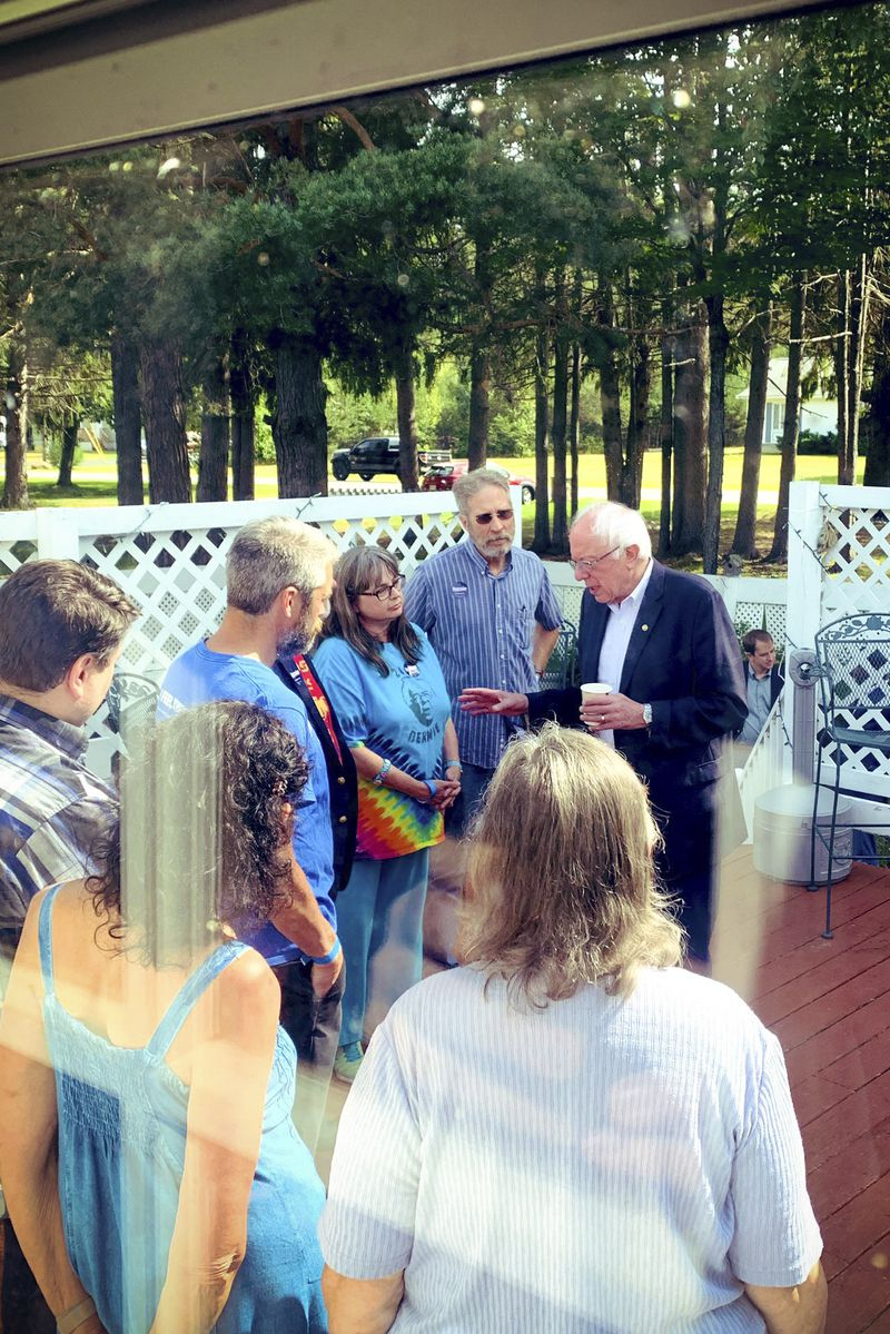 Bernie Sanders speaks to a supporters while standing outside on a deck.