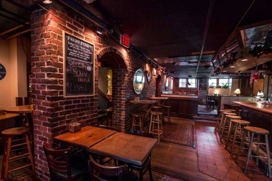 Dim lighting reveals exposed brick and wooden tables inside Grendel's Den, a subterranean bar in Cambridge's Harvard Square