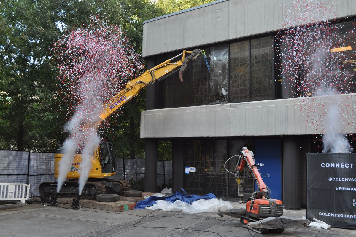 A crane with a concrete ball hits a glass window on the second floor.