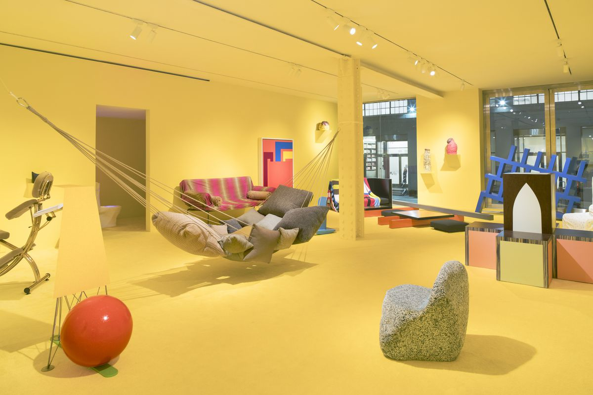 A hammock made from pillows, a chair carved from a boulder, a massage chair, and a bench made from wood boxes sit inside an art gallery with yellow walls.