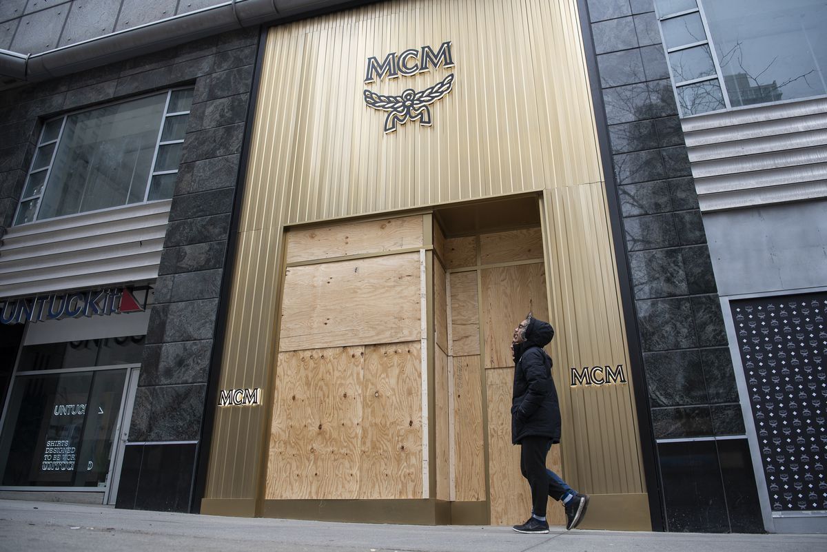 A person walks on Saturday in front of the boarded up windows of MCM, a luxury travel goods store at 540 N. Michigan Ave.