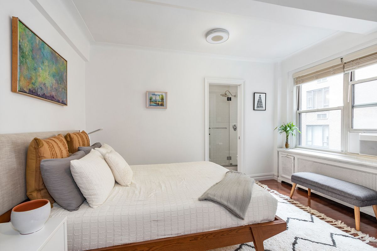 A bedroom with a medium-sized bed, hardwood floors, large windows, and beamed ceilings.