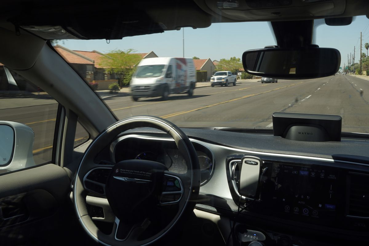 A Waymo minivan moves along a city street as an empty driver's seat and a moving steering wheel drive passengers during an autonomous vehicle ride in Chandler, Ariz. The U.S. government's highway safety agency wants to examine patterns involving crashes of fully autonomous vehicles or partially automated driver assist systems.