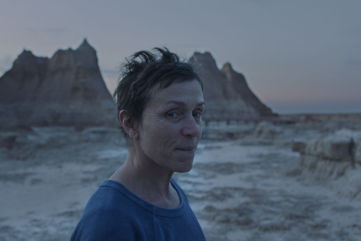 A white woman stands against the backdrop of the Badlands, with a small smile on her face.