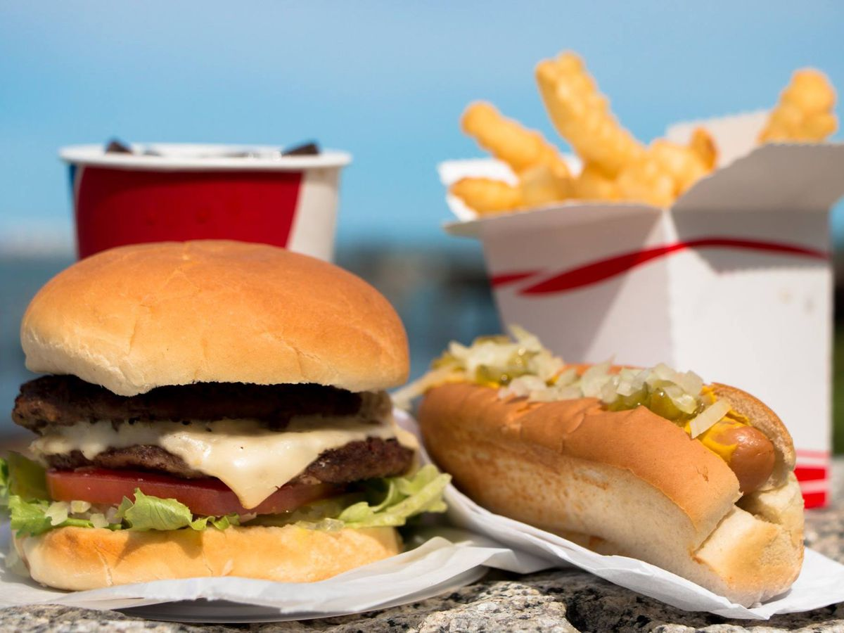 A double cheeseburger, hot dog topped with relish, container of fries, and cup of soda sit outside in the sun