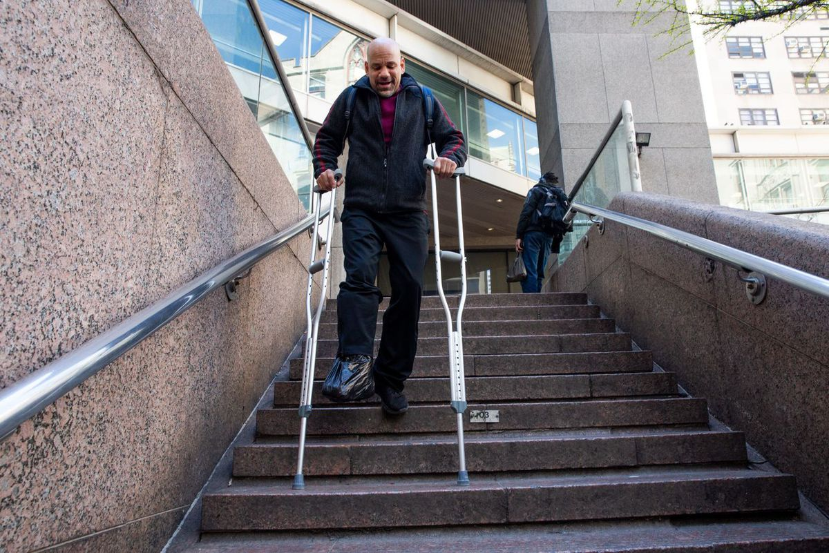 John, 56, makes his way down the stairs at the 68th Street station.