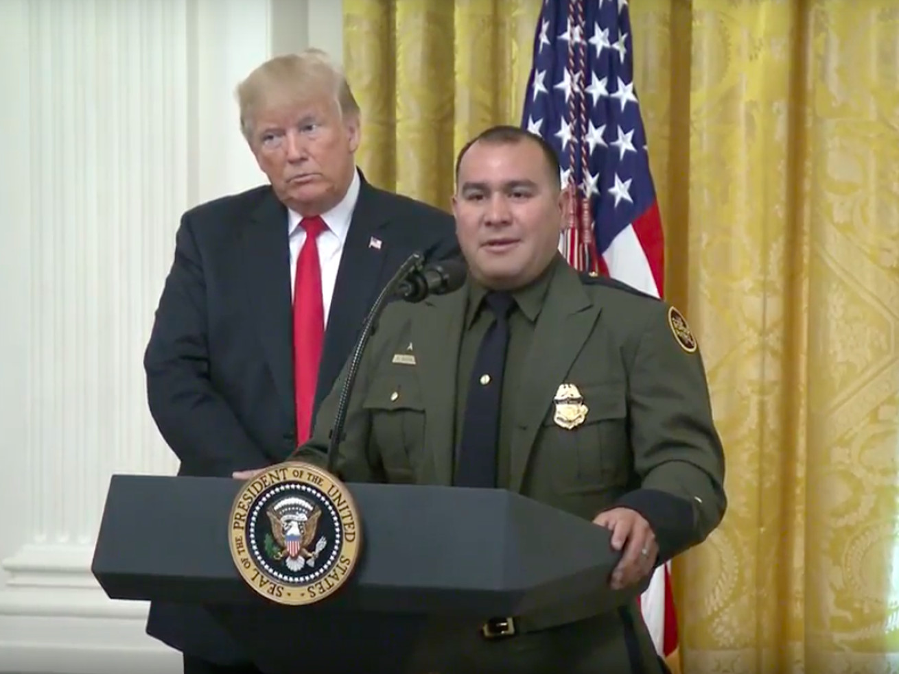 "President Donald Trump with Border Patrol agent Adrian Anzaldua, whom Trump praised to an audience of Immigration and Customs Enforcement (ICE) and Customs and Border Protection (CBP) officials by reassuring them he ""speaks perfect English."""