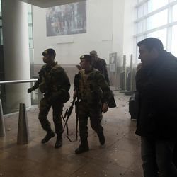 In this photo provided by Georgian Public Broadcaster and photographed by Ketevan Kardava, armed security personnel are seen in Brussels Airport in Brussels, Belgium, after explosions were heard Tuesday, March 22, 2016. A developing situation left a number dead in explosions that ripped through the departure hall at Brussels airport Tuesday, police said. All flights were canceled, arriving planes were being diverted and Belgium's terror alert level was raised to maximum, officials said.