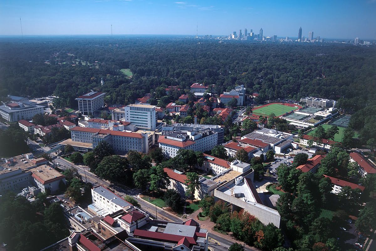 An aerial view of the campus with forests and the skyline beyond.