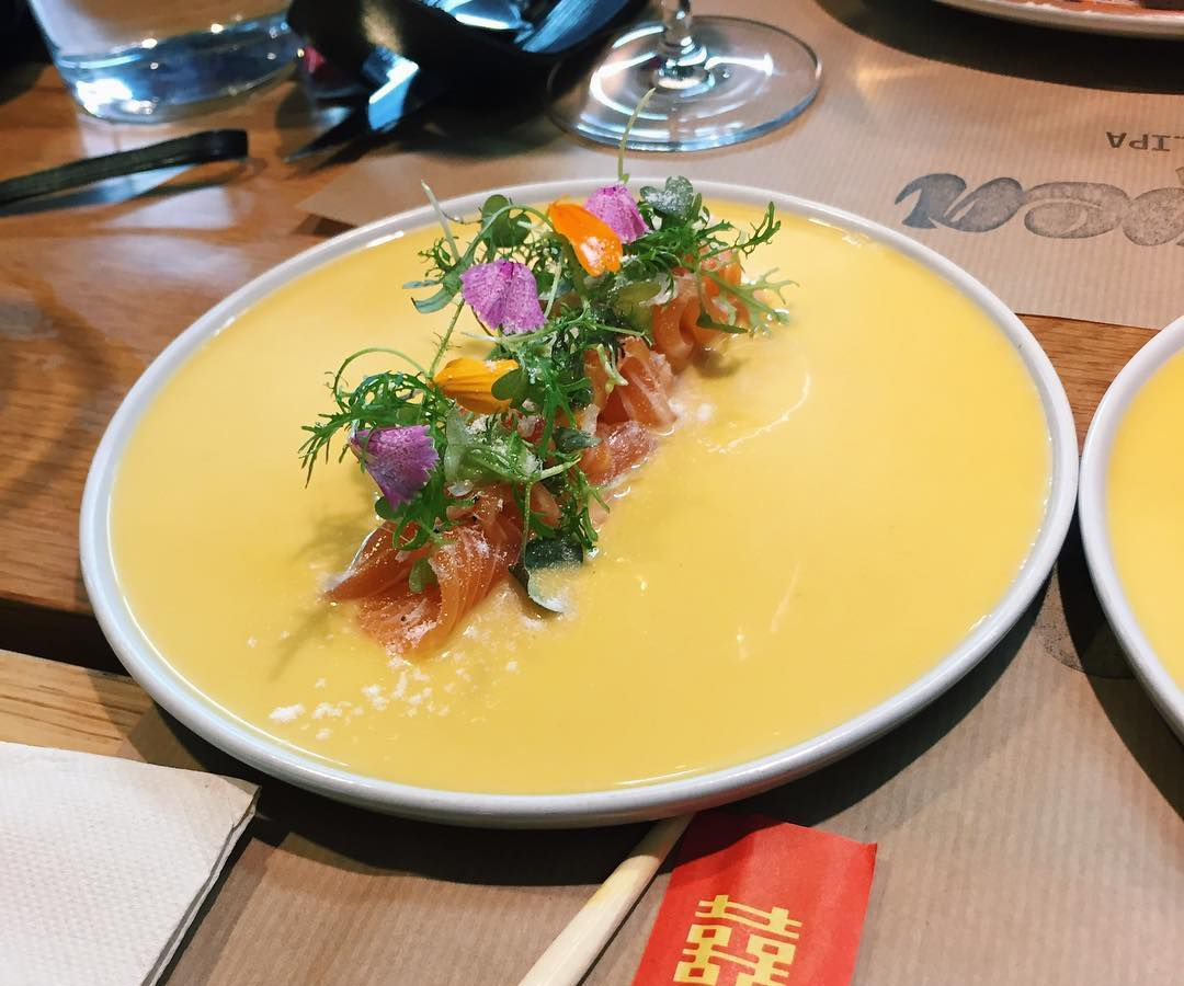 A round plate with a row of wild salmon tiradito in the center surrounded by yellow mango leche de tigre