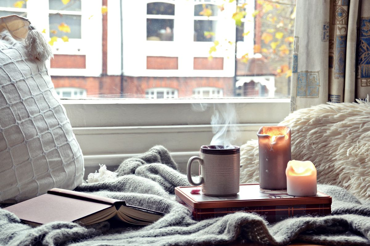 Cozy pillows and blankets sit adjacent to a window that looks out onto an urban street. A book is overturned on the blanket and a tray holds two lit candles and a steaming mug of liquid.