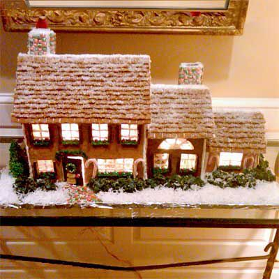 Detailed gingerbread house with snowy roof.