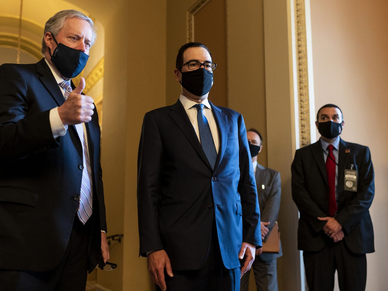 Meadows, wearing a dark suit, light blue tie, and black cloth mask, gives a thumbs up. Mnuchin, in a navy suit, dark blue tie, and black face mask, stands solemnly with his hands stiff against his sides.