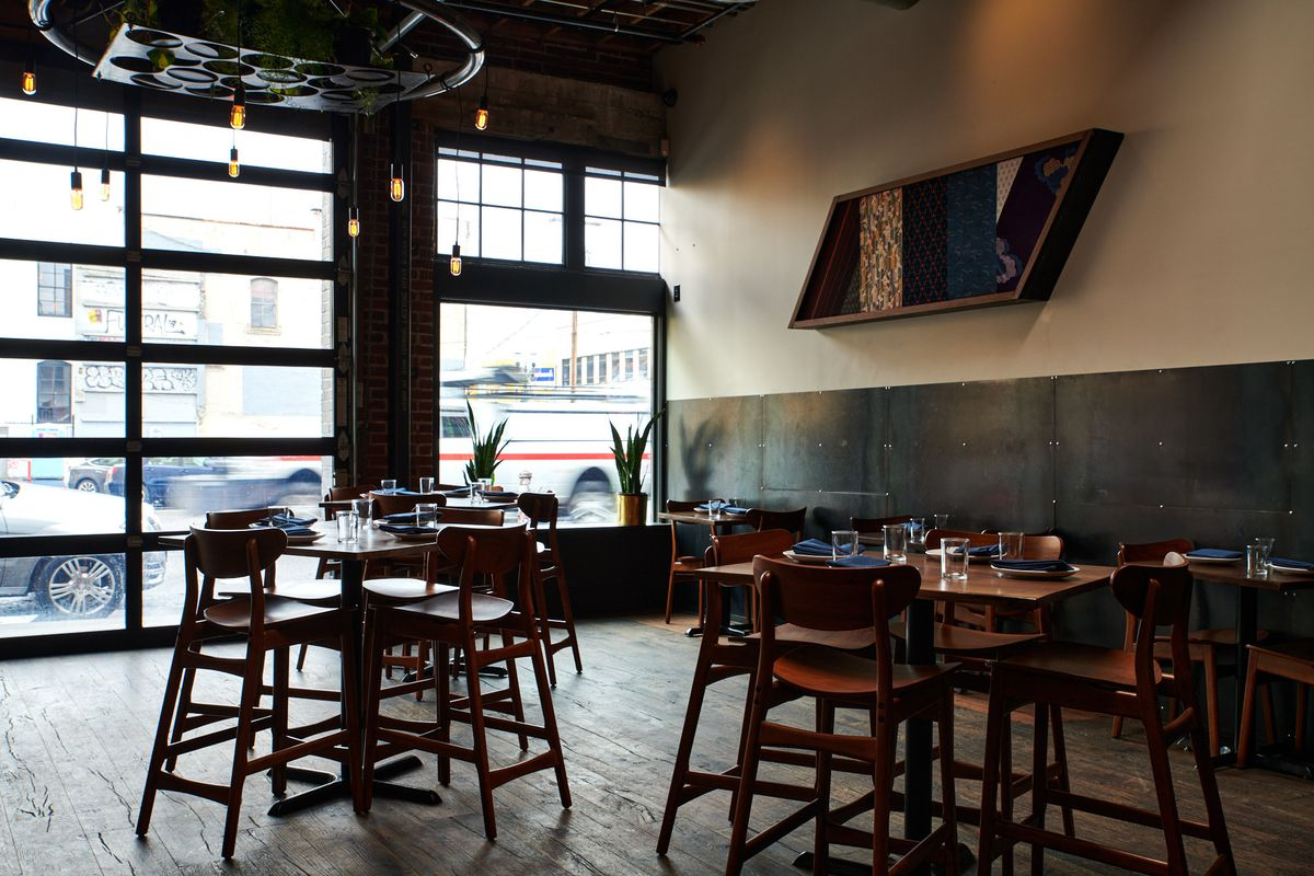 On a white wall next to the windows, a wooden parallelogram-shaped sign is filled with various Japanese fabrics. Below, a handful of tall, four-seat bar tables sit on unfinished wooden floors.