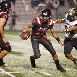 West's Isaiah Suesue (15) moves past Roy's Alex Johnson (26) during a high school football game Friday, Sept. 10, 2021, at West High School in Salt Lake City.