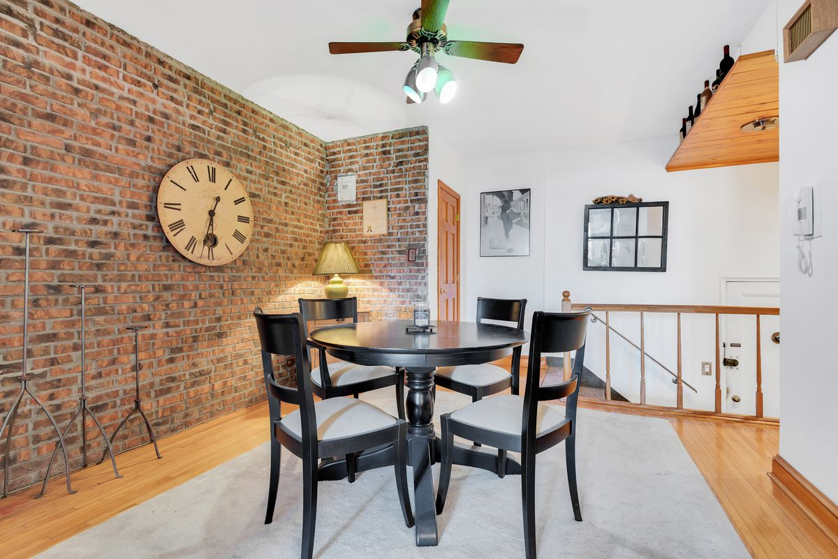 A lofted area with exposed brick, a large wooden  clock on the wall, a ceiling fan, hardwood floors, and a round dining table.