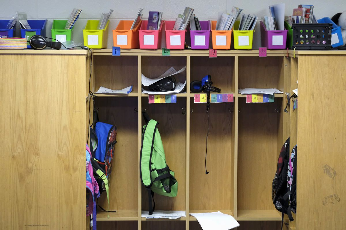 Multicolored file-holders sit atop four student cubbies holding papers, and backpacks in a classroom