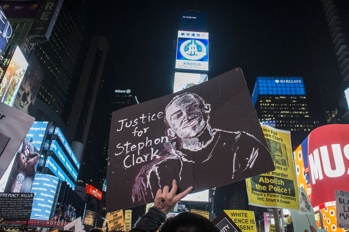 "A protester on a nighttime New York street holds up a sign reading, ""Justice for Stephon Clark."""