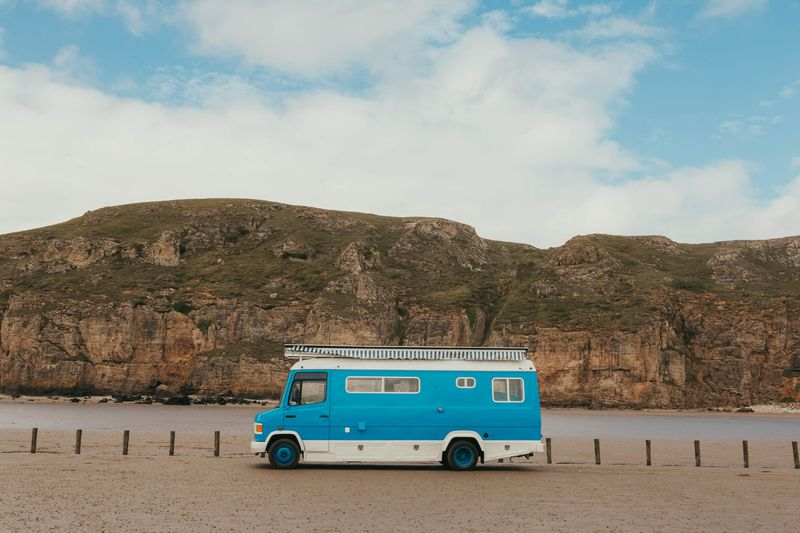 A side view of a blue camper with white trim. The camper sits on sand with cliffs in the background.