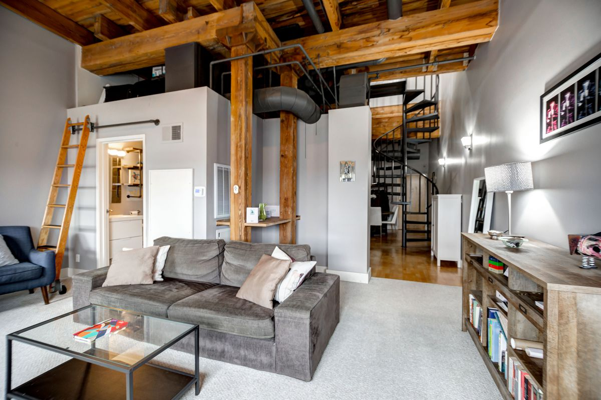 A loft with a spiral metal staircase and wood ladder leading to the second floor. On the first level there's a gray couch and wood credenza on the carpeted floor.