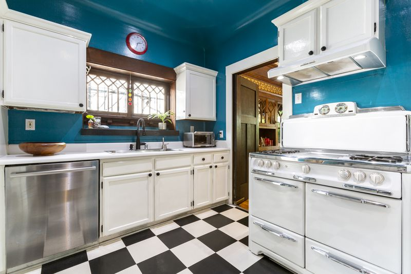 The kitchen has white cabinets and blue walls.