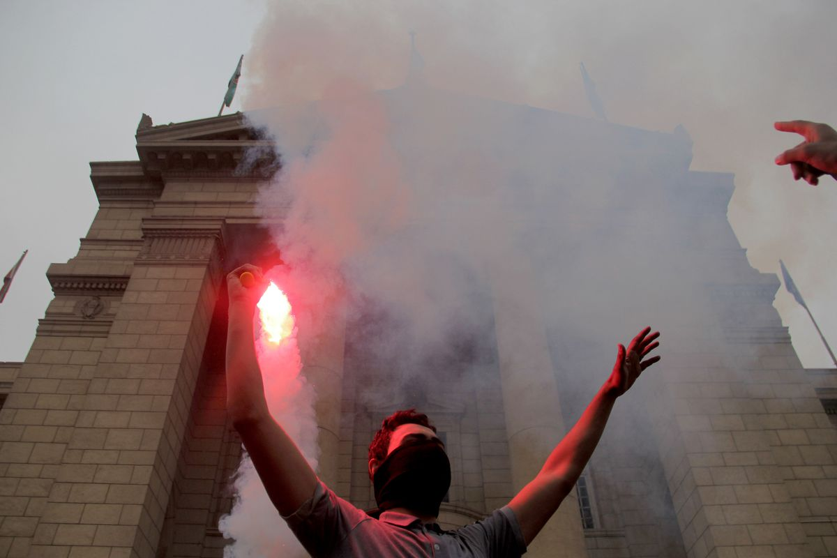 An Egyptian student holds up a flare during a protest against court verdict acquitting former President Hosni Mubarak, at the Cairo University campus on December 3, 2014, in Cairo, Egypt.